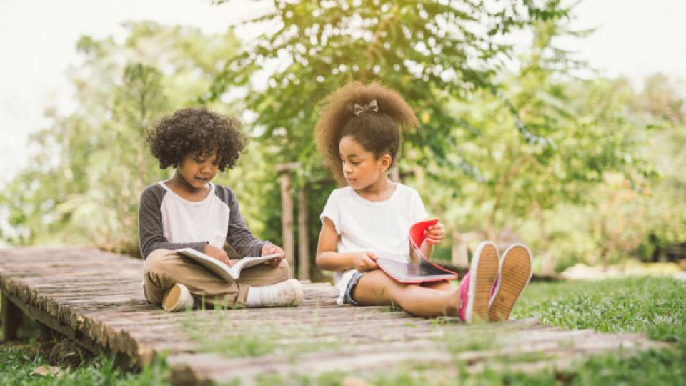 menina-pequena-crianca-lendo-livro-entre-jardim-prado-verde-com-o-conceito-de-educacao-de-amigo_29360-66